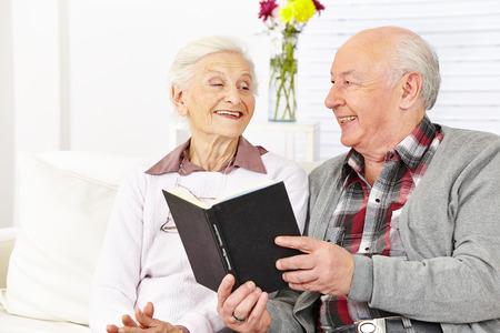 ancianos felices: Pareja de ancianos leyendo un libro en una casa de retiro