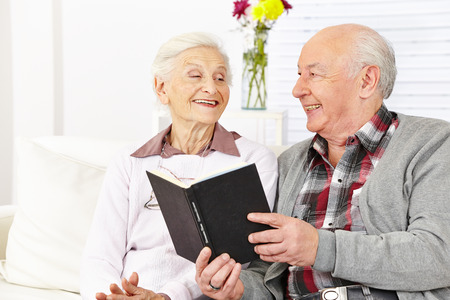 Senior citizen couple reading a book in a retirement home