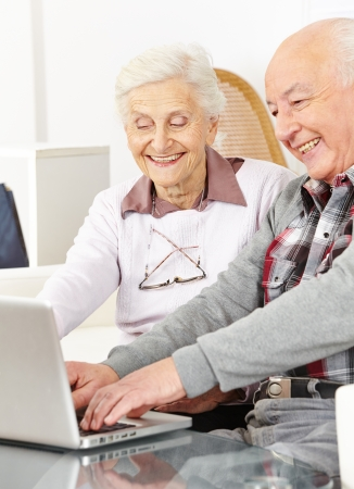 social apartment: Happy senior couple chatting over internet with laptop computer