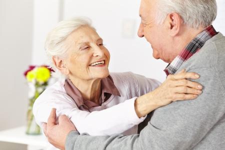 Twee gelukkige senioren dansen en lachen in een dansles