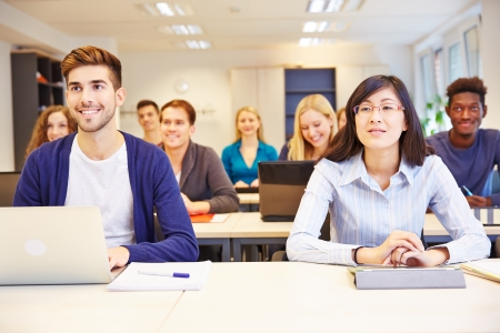 Many smiling students learning in a university class photo