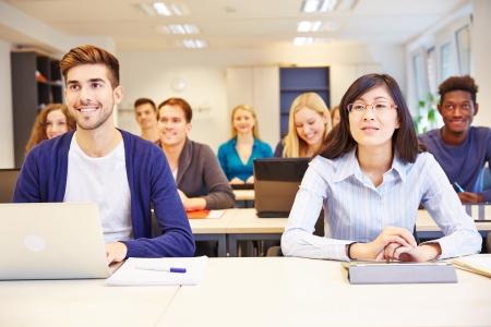 curso de capacitacion: Muchos estudiantes sonrientes aprendizaje en una clase universitaria