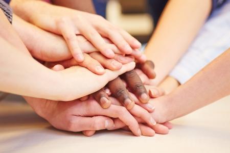 mãos: Motivação e trabalho em equipe com muitas mãos empilhadas na escola
