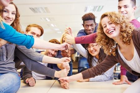Vele handen gestapeld als symbool voor teamwork in een universiteit klasse