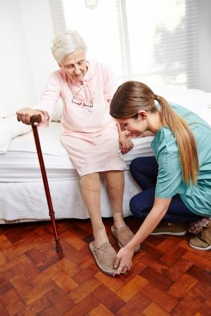 Verzorger helpt dressing senior vrouw op haar bed thuis Stockfoto