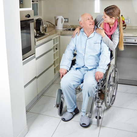 social work aged care: Family with senior man in wheelchair at home in the kitchen