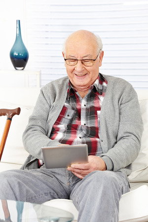 Old senior man using tablet computer to surf the internet at home photo