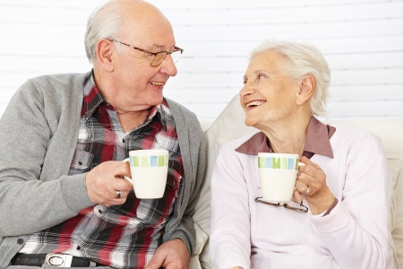 Happy senior citizen couple drinking coffee together photo