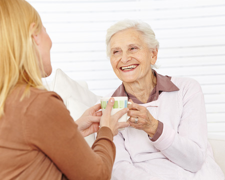Family with senior woman drinking coffee in a retirement home photo