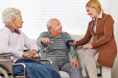 eldercare: Woman measuring blood pressure on her senior parents at home