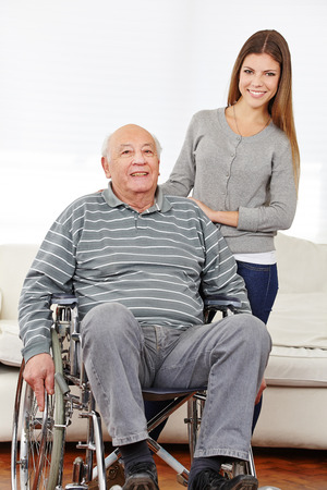 social apartment: Portrait of a happy granddaughter with her grandfather in a wheelchair