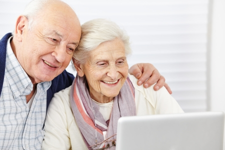 a person: Happy senior couple surfing the internet with laptop computer