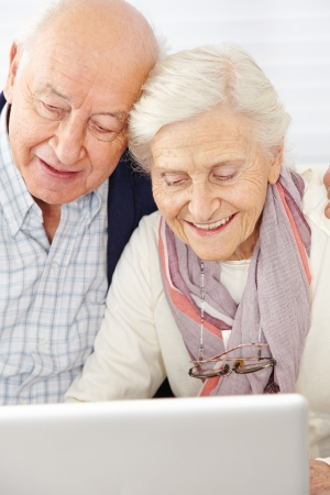 Happy senior couple using social media with laptop computer photo