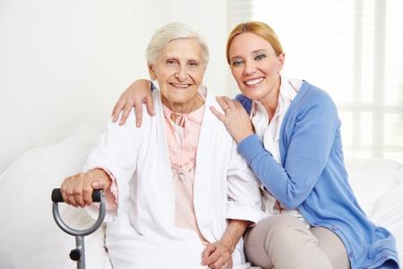 幸せの年配の女性は自宅で家族のベッドに座ってください。