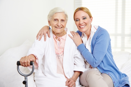 nursing staff: Family with happy senior woman at home sitting on the bed Stock Photo