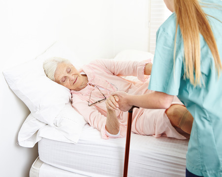 bedridden: Caregiver helping senior woman in nursing home out of bed Stock Photo