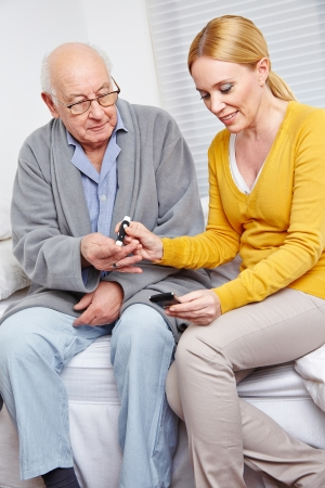 onset: Woman doing blood glucose monitoring for senior man at home Stock Photo