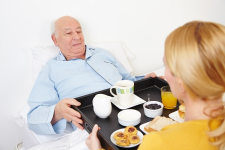 senior eating: Woman giving breakfast to senior citizen in bed at home Stock Photo