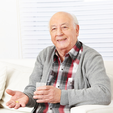 Senior citizen at home taking medical pill with cup of water