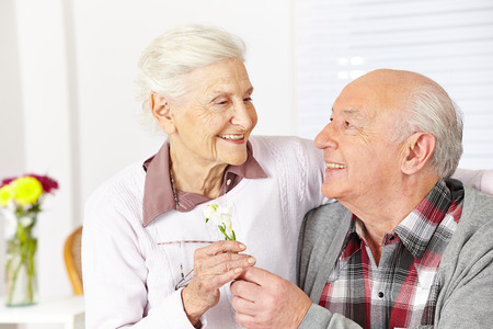 Happy senior citizen giving a freesia flower to smiling woman Stock Photo