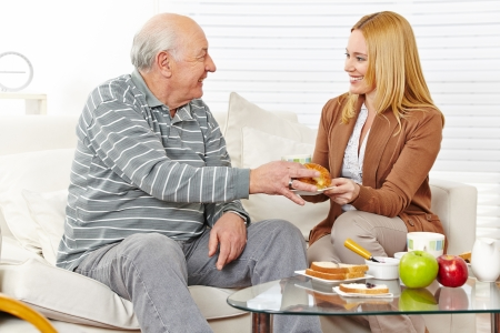Family with senior citizen eating breakfast together at home photo