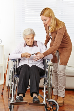 Caregiver woman giving glasses to disabled senior citizen in wheelchair Stock Photo - 24908387
