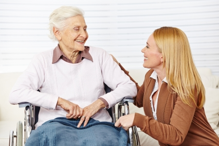 social work aged care: Caregiver woman talking to senior citizen in wheelchair at home