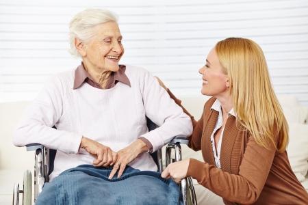 persona en silla de ruedas: Mujer Cuidador hablando de la tercera edad en silla de ruedas en su casa Foto de archivo