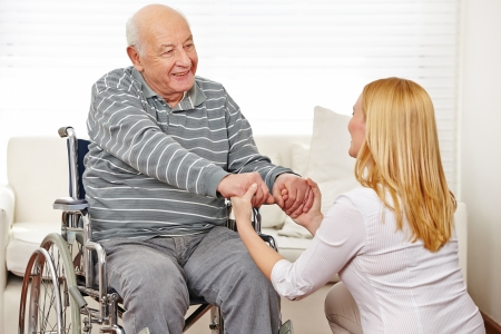 social work aged care: Woman holding hands of old man in wheelchair in a nursing home Stock Photo