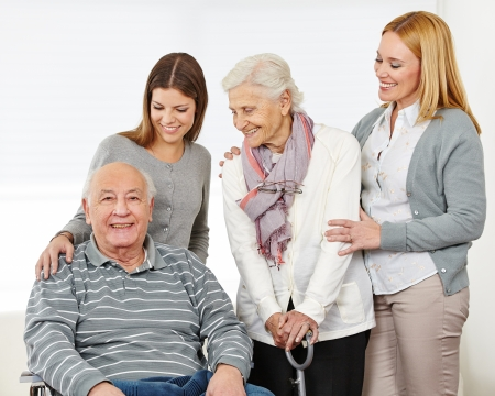 social work aged care: Three generations with happy senior couple at home Stock Photo