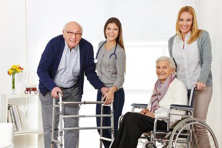 silla de ruedas: Mujer con pareja de ancianos en su casa recibe ayuda de un cuidador
