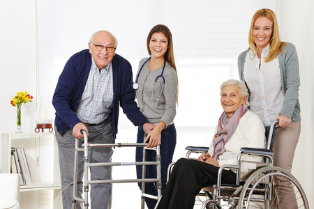 Woman with senior couple at home getting help from a caregiver photo