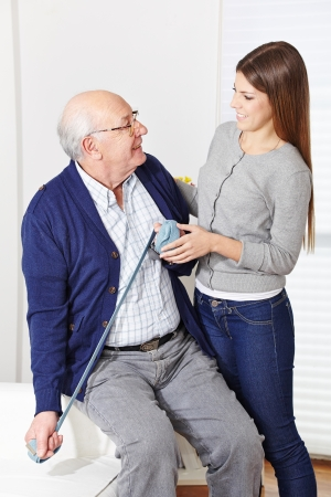 senior home: Senior citizen at physiotherapy with woman in a retirement home