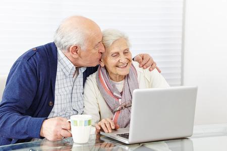 Man kissing happy senior woman at the computer on the cheek photo