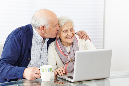 old pc: Man kissing happy senior woman at the computer on the cheek