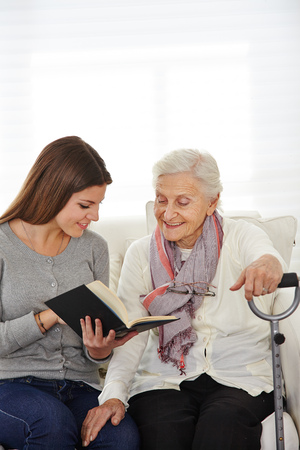 cares: Young woman in community service reading books to senior citizens Stock Photo