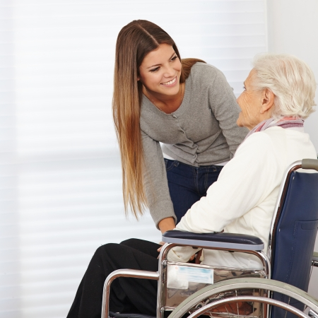 Young woman talking to smiling senior citizen in a wheelchair photo
