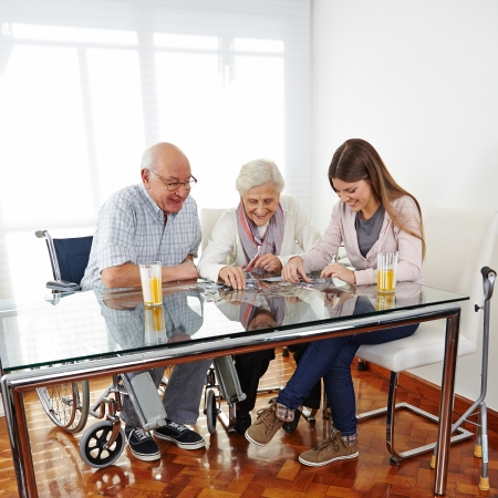 community service: Family with happy senior couple playing jigsaw puzzle at home Stock Photo
