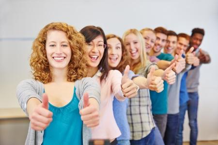 Veel tiener in een rij houden duimen omhoog voor felicitatie