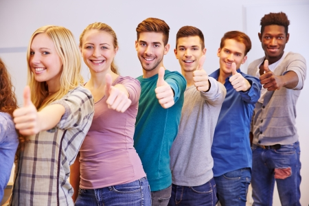 teenagers laughing: Many happy students holding their thumbs up in a university