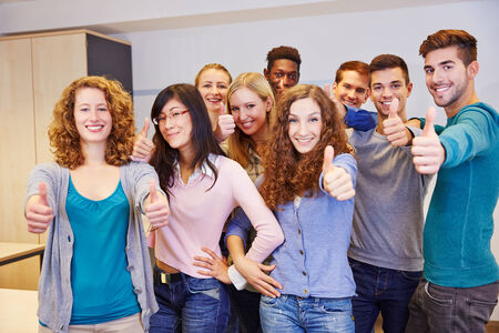 Group of teenager in a school classroom holding their thumbs up photo