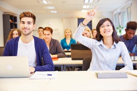アジアの学生が大学の教室で彼女の手を上げる 写真素材