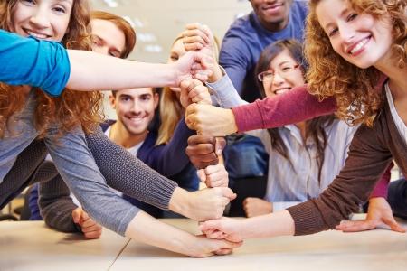 Studenten stapelen vuisten voor samenwerking en teamwork in een universiteit