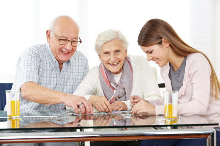 senior citizens: Couple senior citizens playing with a jigsaw puzzle with her granddaughter