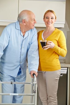Woman with senior man and his walker in the kitchen photo