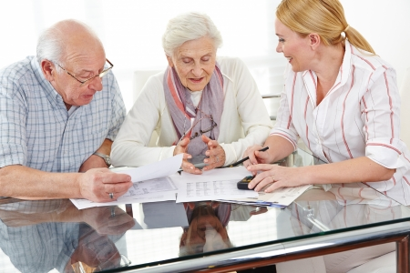 Senior couple getting financial consultation from insurance woman photo