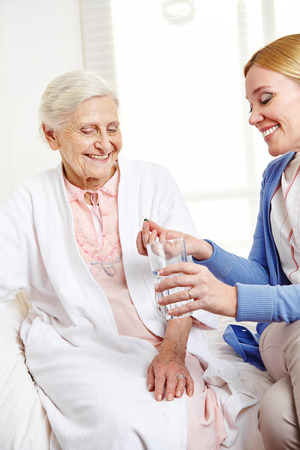 Woman offering pill to sick senior citizen at home photo