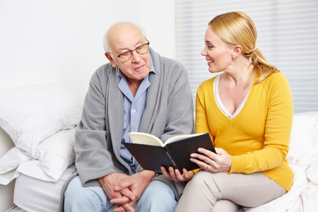 cares: Woman reading a book to a senior citizen man in nursing home