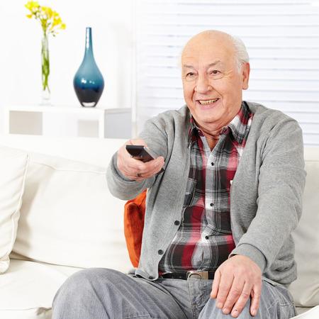 ver tv: Feliz el hombre de la tercera edad viendo la televisión con control remoto