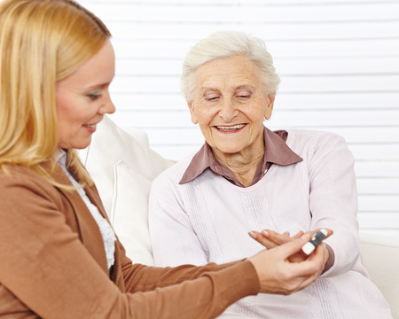 diabetes: Woman doing a blood sugar measurement for senior citizen with diabetes Stock Photo